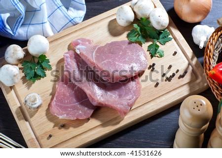 Fresh raw pork meat on wooden board with some fresh veggies around it - stock photo