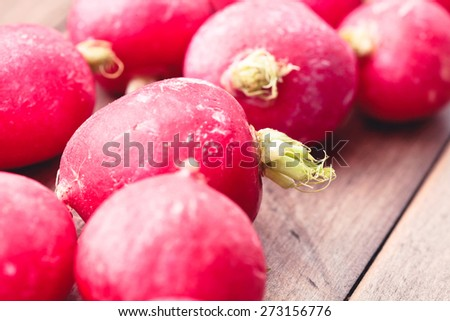 Fresh raw radishes on a wooden surface - stock photo