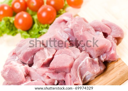 Fresh raw red pork meat pieces for stew and cherry tomato with lettuce green leaf lying on board, preparing meal detail, nobody, horizontal orientation.