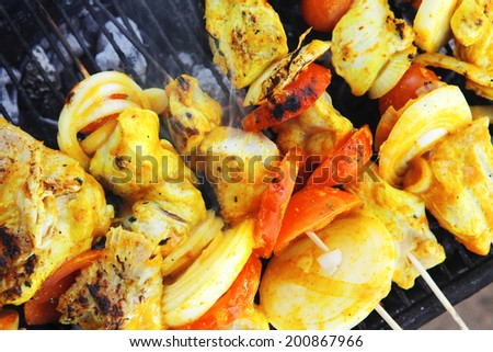 fresh raw roast shish kebab on barbecue grill grid cooked over hot charcoal