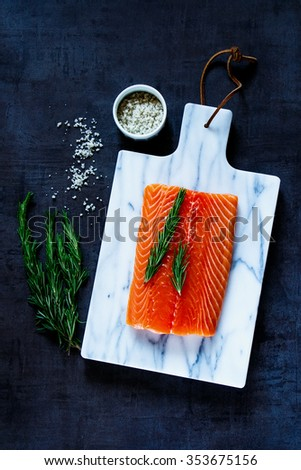 Fresh raw salmon fillet with rosemary and grey salt on marble cutting board. Top view. Background layout with free text space. Healthy food, diet or cooking concept. - stock photo