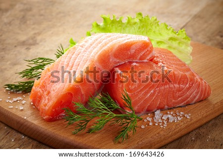 fresh raw salmon on wooden cutting board - stock photo