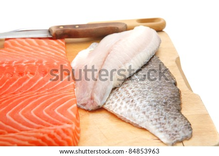fresh raw salmon , red tuna , and sole fish pieces over wooden board isolated on white background - stock photo