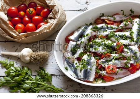 fresh raw sardines on casserole with cherry tomatoes slices, parsley, garlic and potatoes on rustic mediterranean background with white old wooden table - stock photo