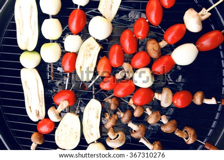 fresh raw tomatoes onion mushroom eggplant on skewers over charcoal on grid over brazier grill - stock photo