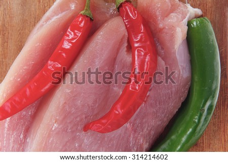 fresh raw turkey meat pieces on wooden cutting plate with red and green hot chili pepper isolated over white background - stock photo
