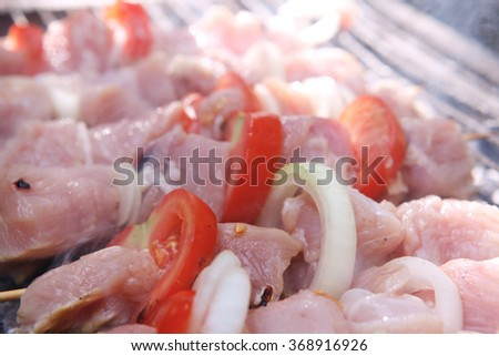 fresh raw turkey pork red meat fillet shish kebab on wooden skewers over vintage kind brazier full with ready charcoal - stock photo