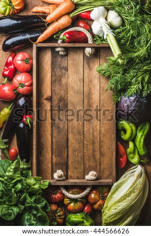 Fresh raw vegetable ingredients for healthy cooking or salad making with rustic wooden tray in center, top view, copy space. Diet or vegetarian food concept, vertical composition - stock photo