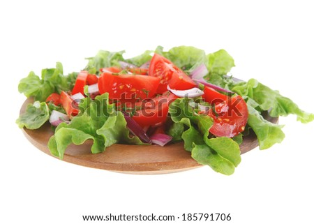 fresh raw vegetable salad with tomatoes and green lettuce on wooden plate isolated over white background - stock photo