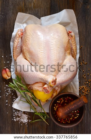Fresh raw whole chicken stuffed lemon and spices for cooking on wooden board. Top view. - stock photo