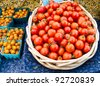 Fresh red and orange tomatoes in a basket at the farmers market - stock photo