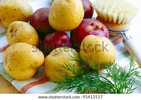 Fresh red and white  potatoes with scrub brush on a striped linen towel and cutting board. - stock photo