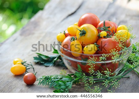 Fresh red and yellow tomatoes in a glass bowl on rustic table