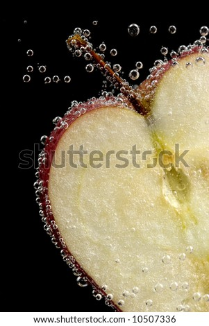 fresh red apple under the water with bubbles - stock photo