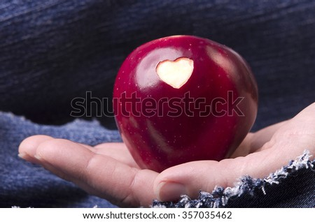 Fresh red apple with a heart shaped cut-out in woman hand on denim, jeans background. GMO free genetically modified organisms. Mothers day - stock photo