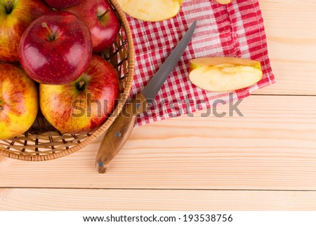 Fresh red apples in basket on wood. Whole background.