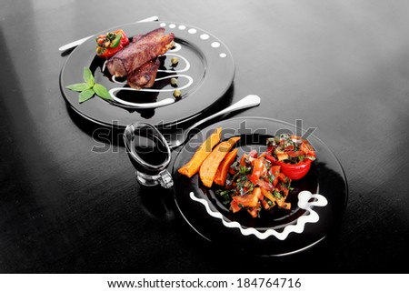 fresh red beef meat steak barbecue garnished vegetable salad sweet potato and basil on black plate over black wooden table with bbq sauce in sauceboat - stock photo