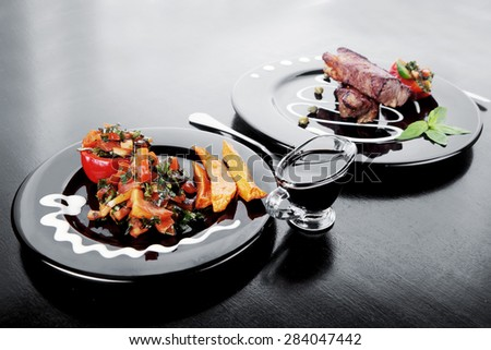 fresh red beef meat steak barbecue garnished vegetable salad sweet potato and basil on black plate over black wooden table with bbq sauce in sauce boat - stock photo