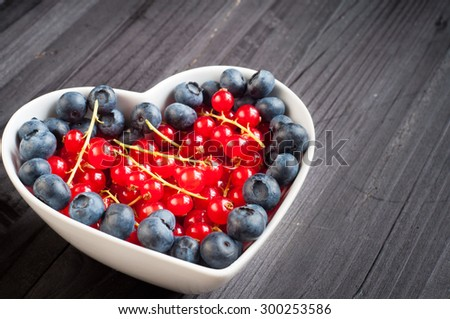Fresh red berries and blueberries served in a heart shaped bowl on a black wooden table.
