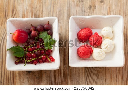 Fresh red berries and small  balls of a delicious ice-cream white square bowls on a vintage wooden table - stock photo