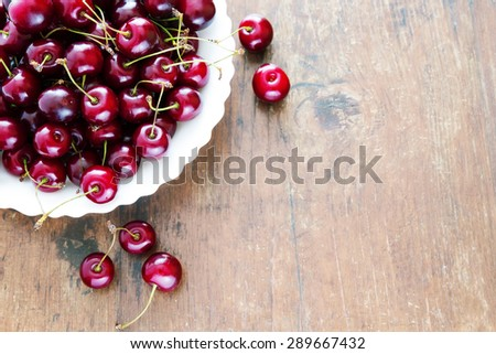 Fresh red cherries in bowl on a wooden table - stock photo