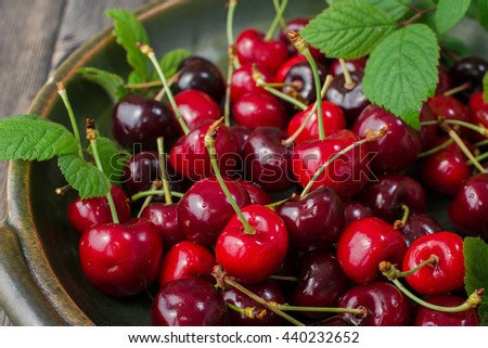 fresh red cherries on an old wooden table with green leaves, rustic style - stock photo