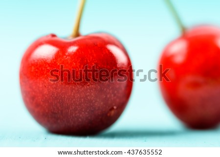 Fresh Red Cherry Fruit On Turquoise Background - stock photo