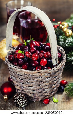Fresh red cranberries in a basket with juice, spices and pine branches - stock photo