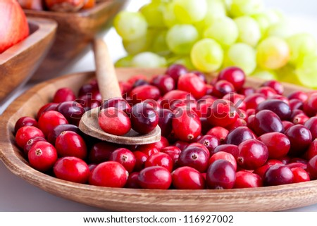 Fresh red cranberries in the wooden bowl with spoon - stock photo