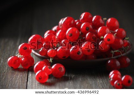 Fresh red currants in plate on dark rustic wooden table. Shallow DOF. - stock photo