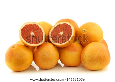 fresh red grapefruits and a cut one on a white background - stock photo