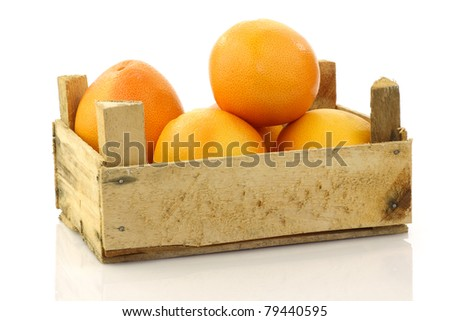 fresh red grapefruits in a wooden box on a white background