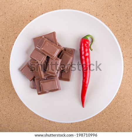 Fresh red hot chili pepper with chocolate on plate, over wooden background. - stock photo