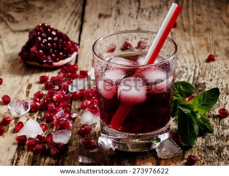 Fresh red juice cocktail with pomegranate seeds, mint and ice, selective focus - stock photo