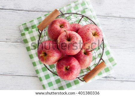 Fresh red juicy apples in a basket on a green textile on a wooden background, top view - stock photo