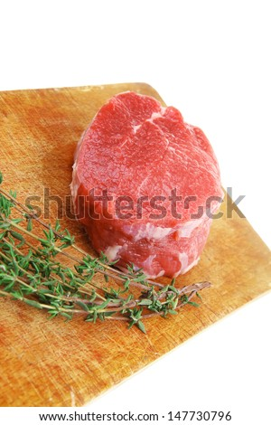 fresh red meat : raw beef fillet on wooden board with thyme ready to prepare . isolated over white background - stock photo