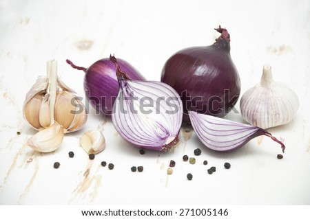 Fresh red onions and garlic on a white wooden background - stock photo