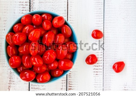 Fresh red organic cherry tomatoes on a wooden background - stock photo