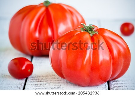 Fresh red organic heirloom tomatoes on white wooden background - stock photo
