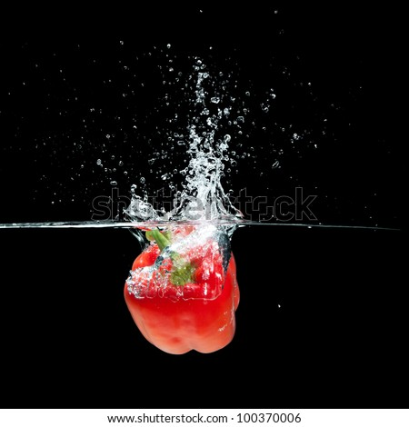 Fresh  red paprika splash in water on black background - stock photo