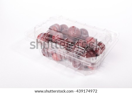 Fresh red plums in plastic container isolated on white background