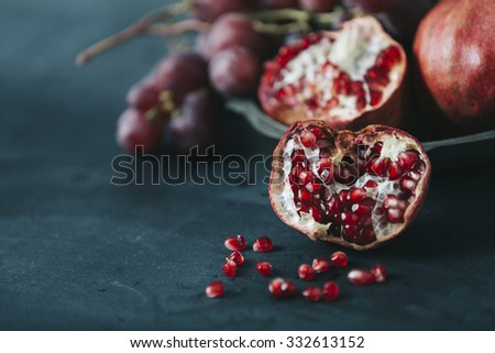 fresh red pomegranate fruit on dark blue colored table - stock photo