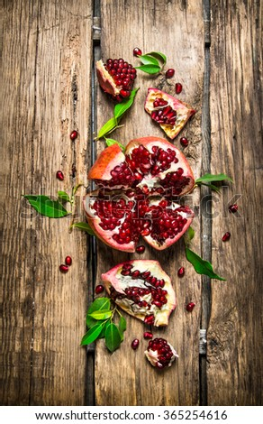 Fresh red pomegranate with leaves. On a wooden background. Top view - stock photo