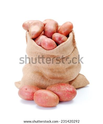 Fresh red potatoes crop in burlap bag - stock photo