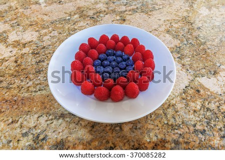Fresh red raspberries and purple blueberries. Presented on white plate with neutral granite background. - stock photo