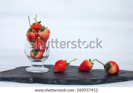 Fresh red ripe strawberries  on black stone isolated on white background - stock photo