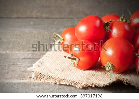 Fresh red ripe tomatoes on rustic wooden background