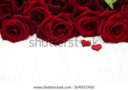Fresh Red roses and wooden heart on a wooden background