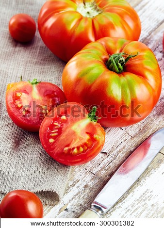 fresh red tomatoes on an old wooden tabletop - stock photo
