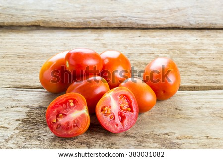 Fresh red tomatoes on wooden table background - stock photo